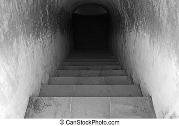 Staircase leading to dark tunnel