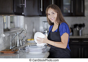Happy housewife doing the dishes - Cute young woman drying...
