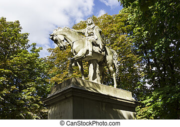 The statue of Louis XIII riding a horse in Place des Vosges,...