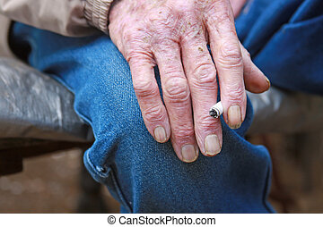 Old Man Smokes Cigarette - An elderly cowboy smokes a...