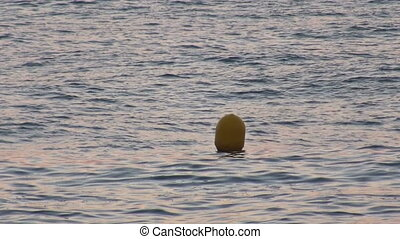 Yellow Buoy bobs on the waves, closeup