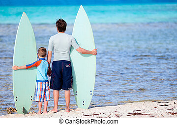 Father and son with surfboards - Back view of father and son...