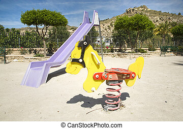kids park - toboggan and jumpping horse at a kids park in...