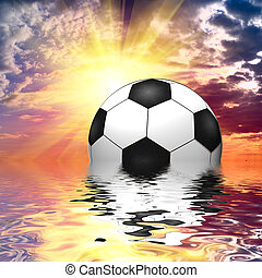 Soccer ball reflected in water over the blue sky with sunset