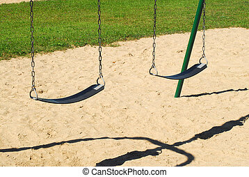 Empty swings on sandy playground