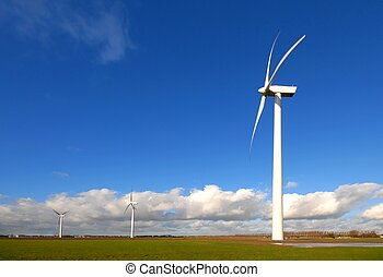Wind Turbines in the grass with blue cloudy sky