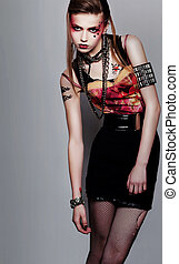 Pretty girl punk with creative make-up and clothes posing