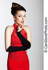 Stylish lovely woman in fashionable red dress looking