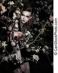Pretty sensual girl in a garden. Creative makeup