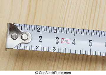 Tape measure closeup on wood background