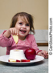 Little Jewish girl dipping apple slices into honey Its the...