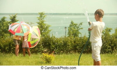 Artificial sunshower - Boy creating summer sunshower by...