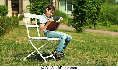 Summer tales - Cute boy sitting on a bench in the park and...