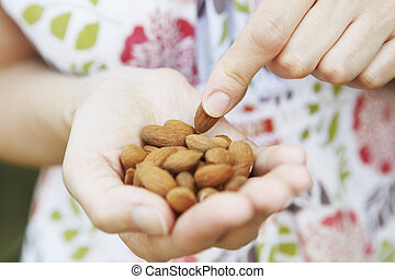 Close Up Of Woman Eating handful Of Almonds