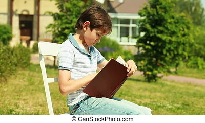 Holiday task - Schoolboy reading a book from his holiday...
