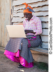 Typing - An african lady is learning the ways of a computer.
