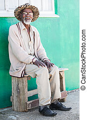 Senior - A old man is sitting on a bench outside of his...