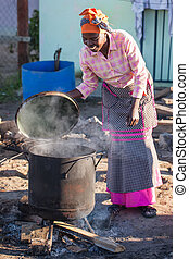 Cooking - An african woman is making food the traditional...