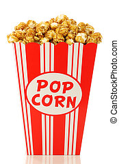 caramel popcorn in a decorative paper popcorn cup on a white...