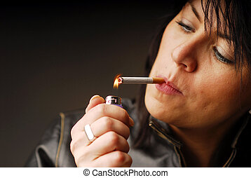 A Woman Smoker - A dark hair woman lighting up her cigarette