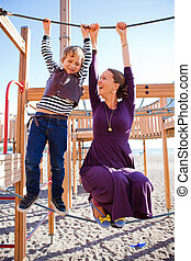 Mother and son playing at playground. - A mother and son...