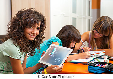 Young girl showing homework on tablet indoors - Young...