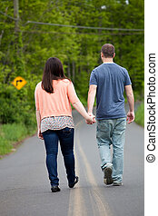 Couple Walking Down the Road Together - Young happy couple...