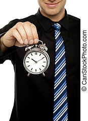 Business executive holding alarm clock Cropped image -...