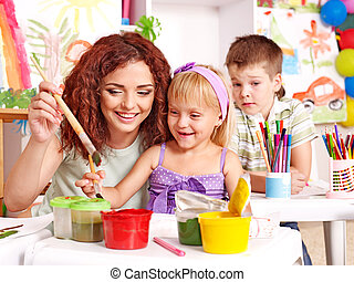 Child painting at easel. - Children with teacher painting at...