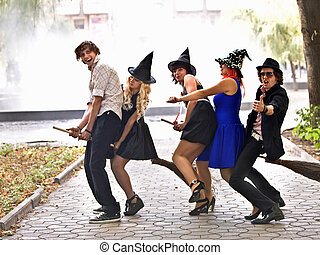 Group of people on broom and halloween witch costume. -...