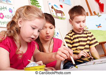 Children painting with teacher. - Children painting with...
