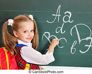 Schoolchild writting on blackboard in schoolroom.