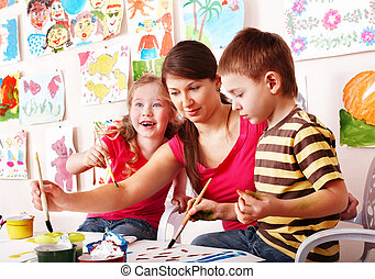 Children with teacher draw paints in play room Child care