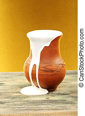 Ceramic jug overflowing cream. - Ceramic jug overflowing...