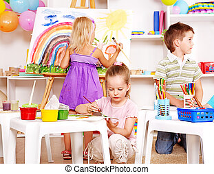 Child painting at easel. - Group children painting at easel...