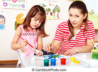 Child painting with mother in preschooler. - Little girl...