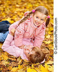 Kids in autumn orange leaves.