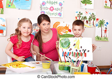 Children painting with teacher in art class.