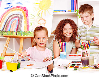 Child painting at easel. - Child with teacher painting at...