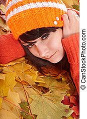Girl in orange hat on leaves with sad face. Autumn...