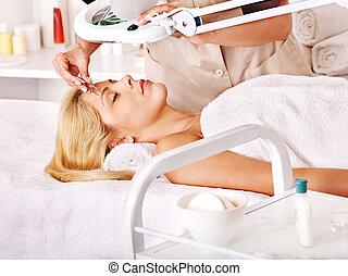 Tweezing eyebrow by beautician. - Woman getting tweezing...