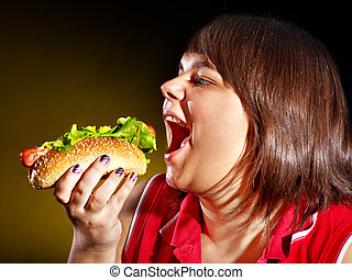 Hungry woman holding hamburger. - Overweight hungry woman...