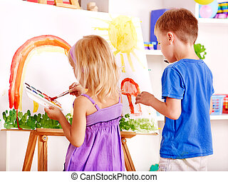 Child painting at easel - Child girl and boy painting at...
