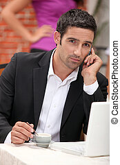 businessman with laptop on the phone having coffee in restaurant