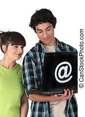 Teenage couple looking at a laptop emblazoned with an @ sign