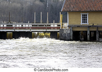 Floodgate letting in water by a small house