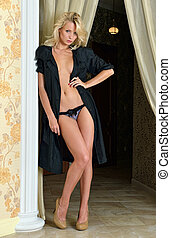Beautiful naked woman in black silk robe in luxury interior....