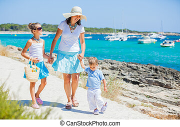 Family of three walking along tropical beach - Young...