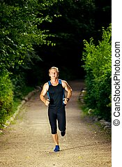 Male Runner in Park - Young athletic man in sportswear...