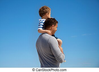 Young Boy Carried by His Father - Young boy carried by his...